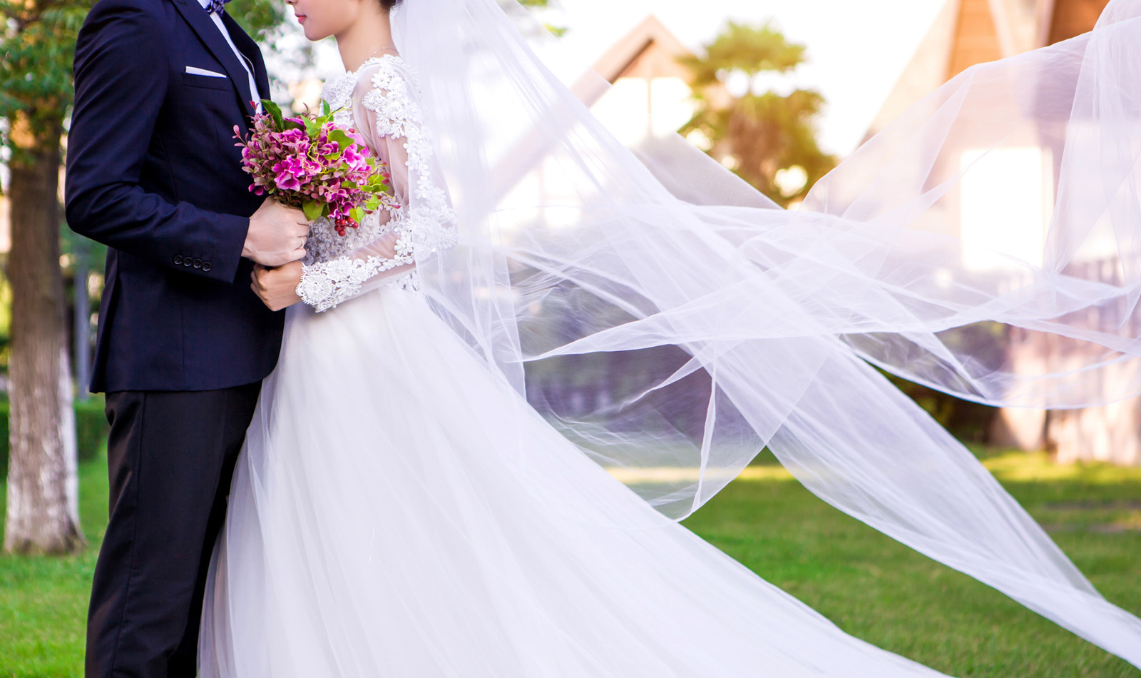 Side view of wedding couple standing at lawn